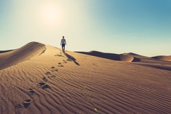 Man in summer clothes with sunglasses is going down the red dune tracing his footprints during sunny day in UAE Liwa desert, at the beautiful rippled sand