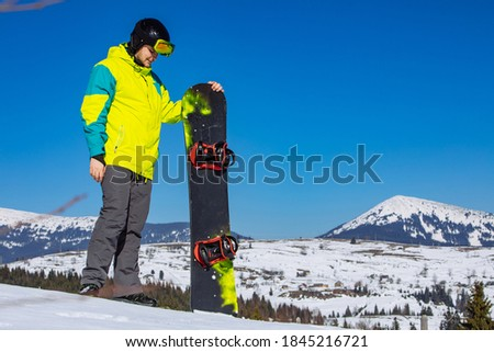 man in sunglasses holding snowboard