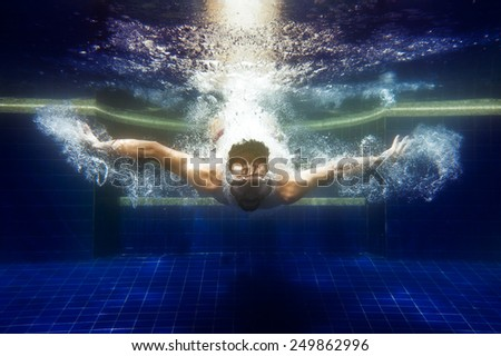 man in sunglasses underwater dives under water in the pool