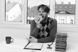 Man in sweater sitting at desk with stack of books on it. Guy bites globe model on light window background. Nerd with bristle and funny face hits the grindstone. Studying and education concept