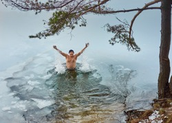 Man in swimming trunks stands in the ice hole under a pine and smiles, raising his hands