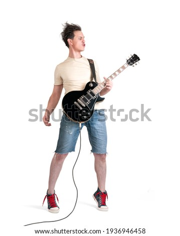 Man in t-shirt and jeans shorts emotionally playing electric guitar, isolated on white background Photo stock ©