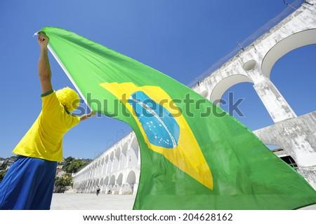 Man in team Brazil kit waving Brazilian flag over Arcos da Lapa Arches Rio de Janeiro Brazil