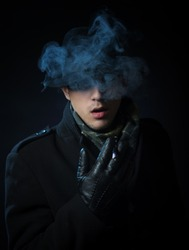 Man in the black trench coat smoking electronic hookah pen in the darkness
