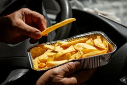 Man in the car eat yummy french fries in aluminium foil tray. Fast food o street food takeaway service concept.