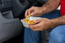 Man in the car eat yummy french fries in aluminium foil tray. Fast food o street food takeaway service concept