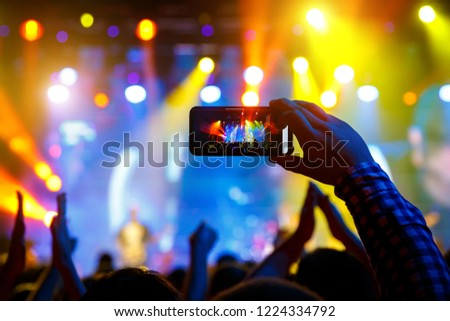 Man in the crowd at a concert make video recordings and pics on a smartphone of published in social media