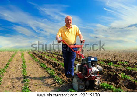 Man in the field with the motor cultivator