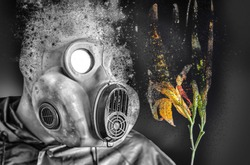 Man in the gas mask holding a burning flower. Radiation influence. Environmental pollution. Chernobyl concept. Dangerous nuclear power. Pollution concept.