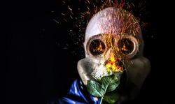 Man in the gas mask holding a burning flower. Radiation influence. Environmental pollution. Chernobyl concept. Dangerous nuclear power. Attack virus protection. Nuclear explosion.