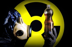 Man in the gas mask holding plastic bottle with dirty water. Radiation influence. Environmental pollution. Chernobyl concept. Dangerous nuclear power. Ecological disaster.