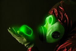 Man in the gas mask holding radioactive luminous apple. Radiation influence. Environmental pollution. Chernobyl concept. Dangerous nuclear power.