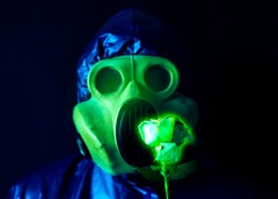 Man in the gas mask holding radioactive luminous flower. Radiation influence. Environmental pollution. Chernobyl concept. Dangerous nuclear power. Ecological disaster.
