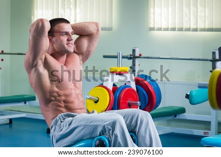 Man in the gym. Working out with weights.Man makes exercises. Sport, power, dumbbells, tension, exercise - the concept of a healthy lifestyle. Article about fitness and sports.