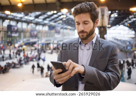 Man in the hall station. Typing text message  on mobile phone #265929026