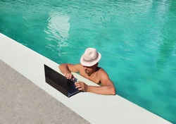 man in the hat works poolside