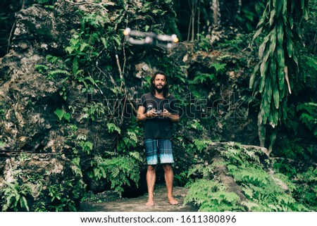 Man in the junbgles flying controlling drone