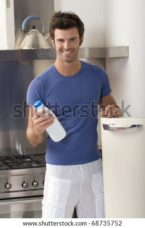 man in the kitchen with a bottle of milk - stock photo