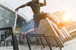 Man in the mid-air. Low angle view of young man in sport clothing jumping while exercising outside