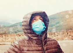 man in the mountain alone looking at the sky while wearing a surgical mask , concept of corona virus and quarantine in winter 2020