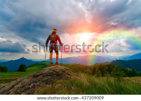 Man in the mountains at sunset looks rainbow in a divine sky