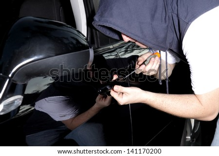 man in the night breaking into a car