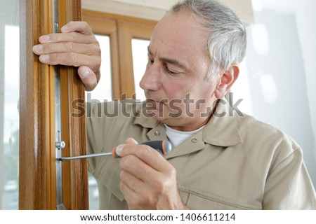 man in the 50s fixing a door