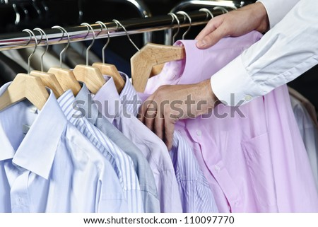 Man in the shop choosing business shirt from another ones.