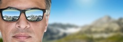 Man in the sunglasses in the beautiful mountain background.