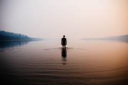 Man in the water knee deep. Smokey atmosphere. Spooky. Reflection in the water. Mountains and trees in the background.
