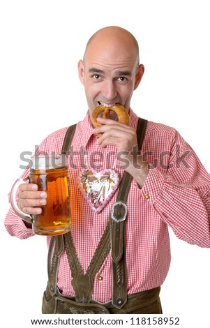 man in traditional bavarian garb with beer eats a pretzel