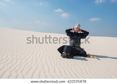 Man in traditional Japanese clothes, concentratedly dresses armor, bogu before  practice of martial arts in a desert. Liberation of the mind in the silence of the wilderness. Shooting at an angle. #633195878
