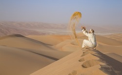 Man in traditional outfit in a desert at sunrise, throwing sand
