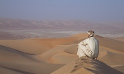 Man in traditional outfit in Empty Quarter Desert that covers a large area of UAE, KSA and Oman