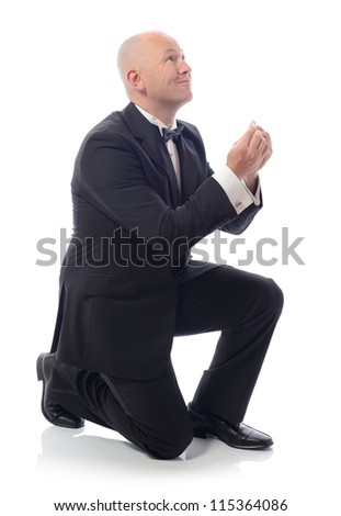 man in tuxedo down on bended knee proposing isolated on white