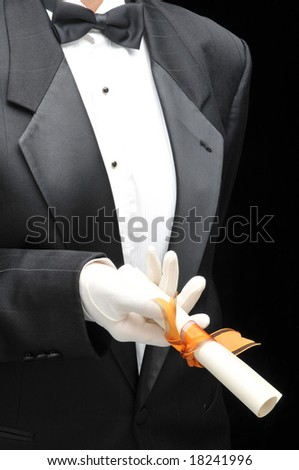 Man in tuxedo handing a diploma in front of body - torso only