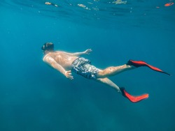 man in underwater in flippers looking at sea bottom