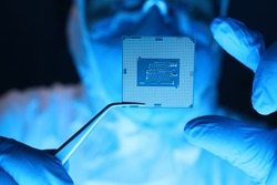 Man in uniform holds microprocessor with forceps. Repair microprocessor electronics electrical equipment. Dust protection at enterprise for creation electronic devices. Chemical elements in design