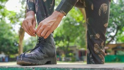 Man in uniform lacing shoes