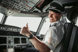 Man in uniform showing ok gesture stock photo. Airways concept
