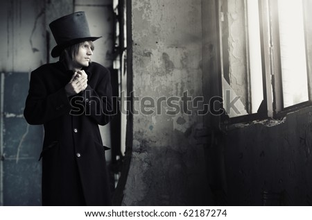 Man in vintage black coat and top hat indoors looking to the window. Artistc colors added