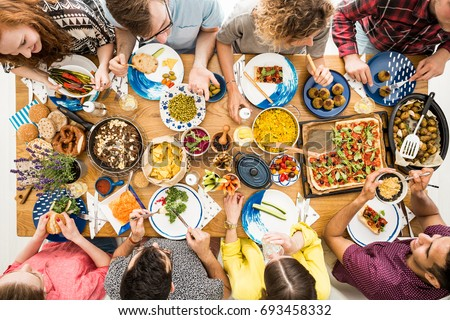 Man in violet shirt eats organic hummus during meeting with vegan friends #693458332