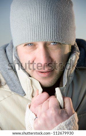 Man in warm gray jacket and hat. Close up.