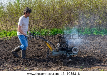 Man in wellingtons with cultivator ploughs ground in sunny day. Land cultivation, soil tillage. Spring work in garden. Gardening concept #1341056318