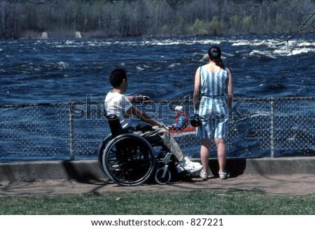 Man in wheelchair and woman watching kayaker on the Ottawa River. Ottawa, Ontario.