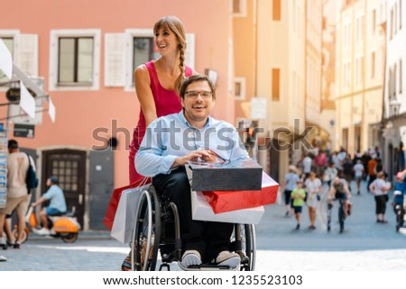 Man in wheelchair being pushed by his friend on a shopping trip with bags #1235523103