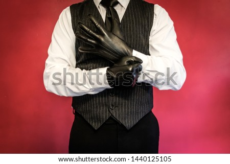Man in White Dress Shirt and Vest Pulling on Leather Gloves
