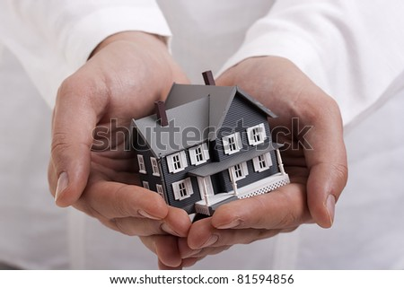 Man in white holding a model of a house in his hands.