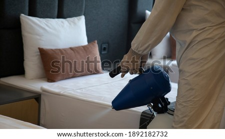 Man in white protective suit in the hotel or hospital sprays hotel rooms, elevator to prevent the contamination of corona virus.Ulv Cold Fogger machine