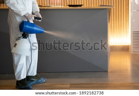 Man in white protective suit in the hotel or hospital sprays hotel rooms, elevator to prevent the contamination of corona virus.Ulv Cold Fogger machine Stockfoto ©